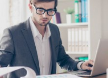 Portrait young handsome businessman with glasses is sitting at the desk in the office workstation and scrutinizing documents